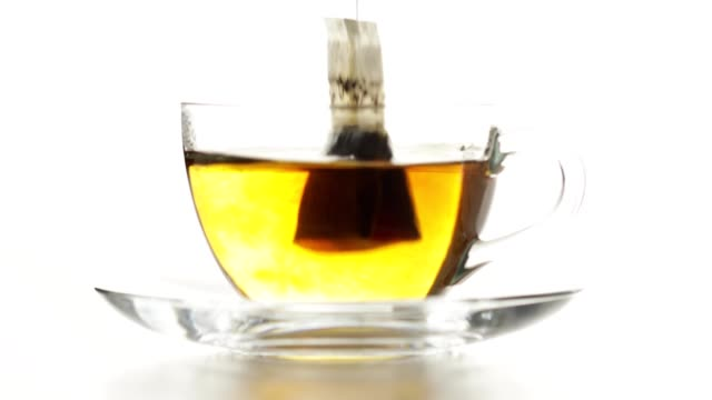teabag is dip into hot water - herb stock videos & royalty-free footage