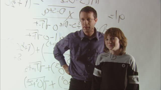 vídeos de stock e filmes b-roll de ms teacher and boy high fiving after solving long math equation using marker on glass/ new york city - inteligência