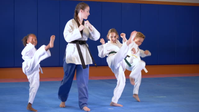 teacher and children in taekwondo class, kicking - 6 7 years stock videos & royalty-free footage