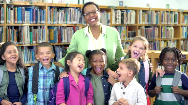 teacher and elementary students in library - 6 7 years stock videos & royalty-free footage