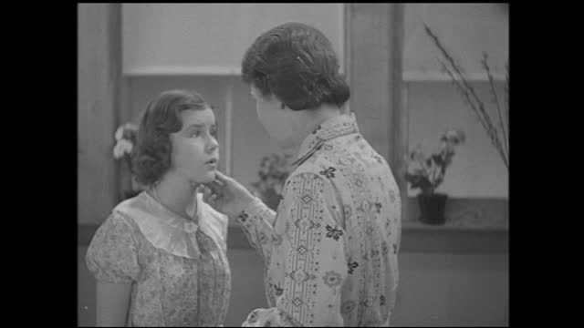teacher and girl looks at the broken vase and talking inside classroom; teacher puts her hand to the girl's cheek - 1940 1949 stock videos & royalty-free footage