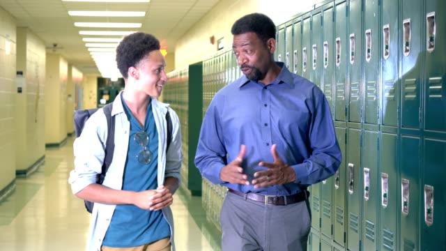 teacher and high school student walking in hallway - head teacher stock videos & royalty-free footage