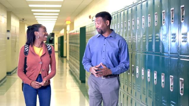vídeos y material grabado en eventos de stock de profesor y estudiante de secundaria caminando por el pasillo - escuela secundaria