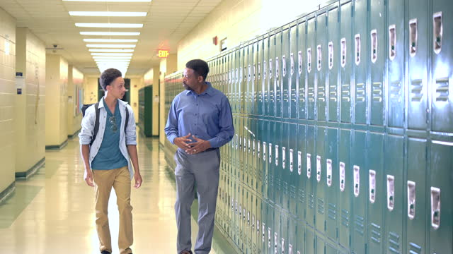 teacher and high school student walking in hallway - locker stock videos & royalty-free footage