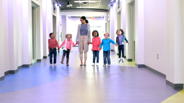 teacher and preschool children holding hands in hallway - child care stock videos & royalty-free footage