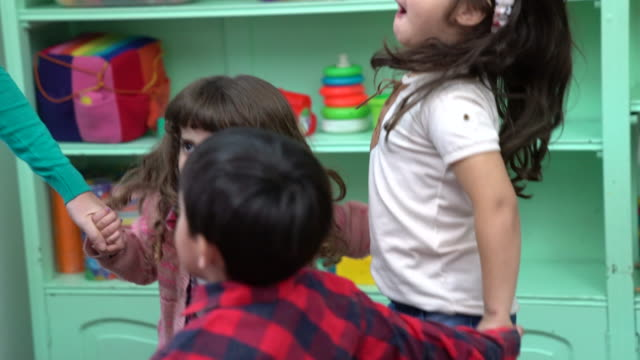 Teacher and preschool kids playing in classroom