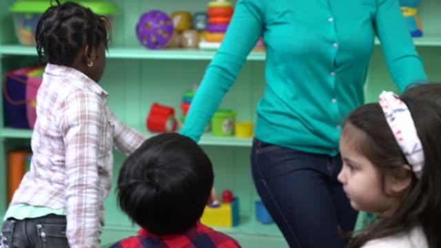 Teacher and preschool kids playing in kindergarten