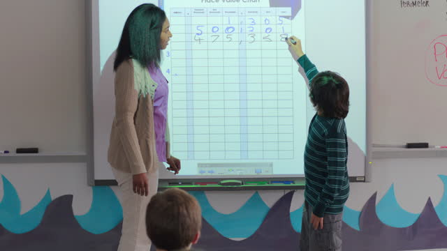 A teacher and student work together to figure out a smart board place value chart.