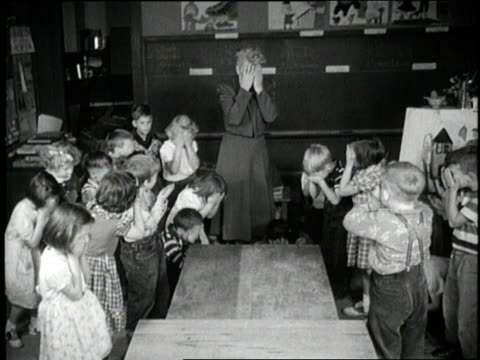 a teacher and students cover their faces and crouch on the floor during an air raid drill - luftangriff stock-videos und b-roll-filmmaterial