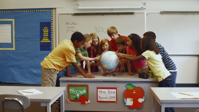 stockvideo's en b-roll-footage met ms zi teacher and students looking over globe in classroom / edmonds, washington, usa  - bureauglobe