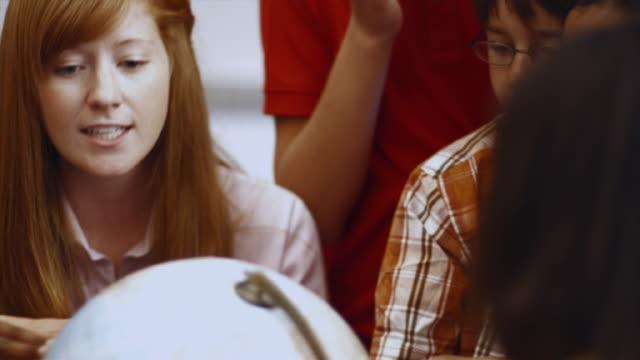 cu tu td pan teacher and students (8-13) looking over globe in classroom / edmonds, washington, usa  - pacific islander teacher stock videos & royalty-free footage