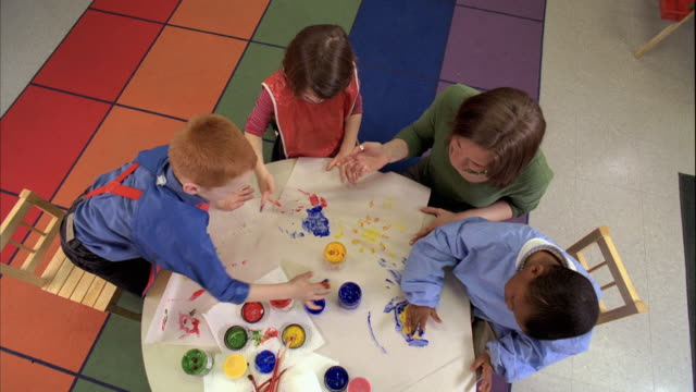 MS CS Teacher and students (5-6) painting with finger paints, Oshkosh, Wisconsin, USA