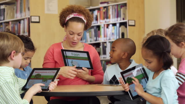 ws teacher and students reading frog life cycle book on tablet computers in library / richmond, virginia, usa - life cycle stock videos & royalty-free footage
