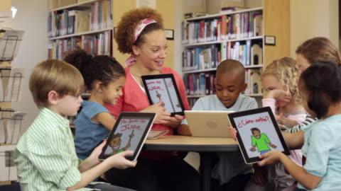 vídeos y material grabado en eventos de stock de ws teacher and students reading spanish book on tablet computers in library / richmond, virginia, usa - maestro
