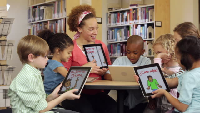 ws teacher and students reading spanish book on tablet computers in library / richmond, virginia, usa - classroom stock videos & royalty-free footage