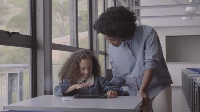 teacher assisting girl in using digital tablet - ausbilder stock-videos und b-roll-filmmaterial