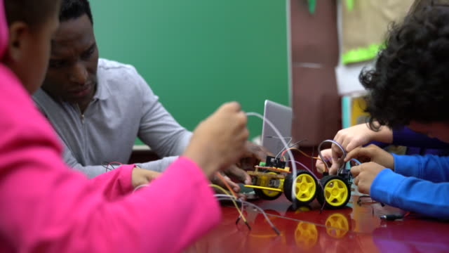 teacher assisting students in preparing toy car - school science project stock videos & royalty-free footage