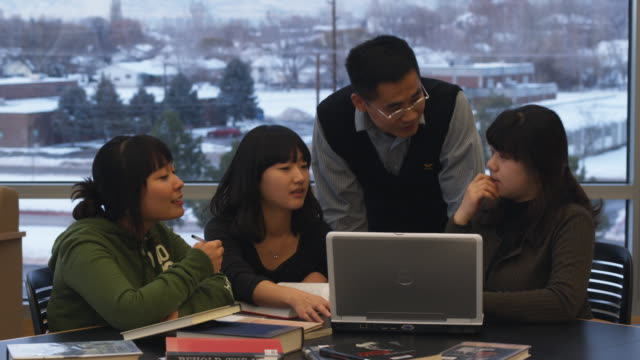 MS PAN Teacher assisting three teenage girls using laptop, Orem, Utah, USA