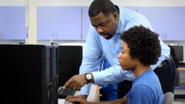 vídeos y material grabado en eventos de stock de profesor ayuda macho estudiante en laboratorio de computación - laboratorio de ordenadores