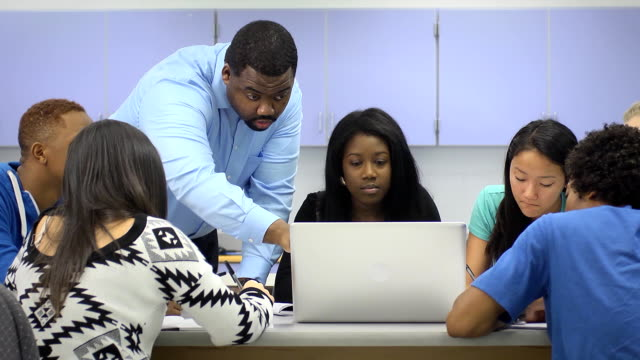 Teacher Assists Multi-Ethnic Students Using Computer