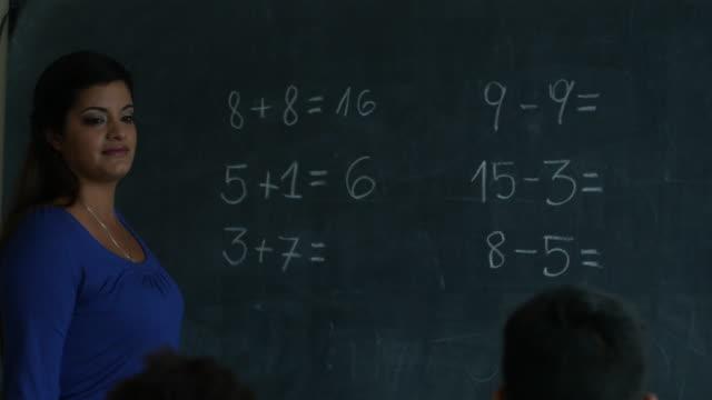 vídeos de stock, filmes e b-roll de professor de uma escola rural ensinando matemática para alunos diversos - afro