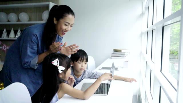vídeos de stock e filmes b-roll de teacher at school helping  little girl and boy  learning technology from laptop - professora