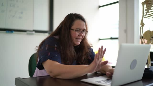 vídeos de stock e filmes b-roll de teacher at school teaching students virtually - professora