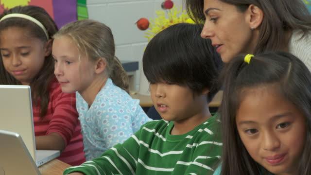 vídeos de stock e filmes b-roll de cu, tu, pan, teacher checking on students (8-13) using laptops in classroom, richmond, virginia, usa - 8 9 anos