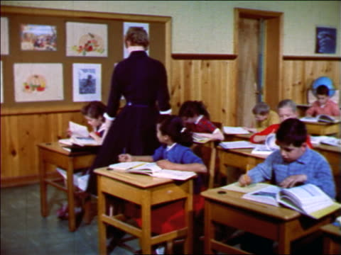 vidéos et rushes de 1957 teacher checking on students' work at desks in classroom / new jersey / industrial - enseignante