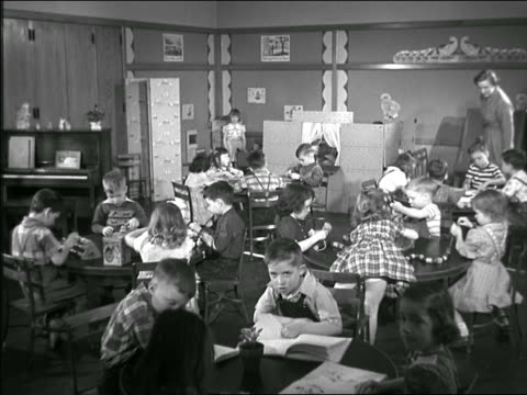 b/w 1949? teacher checks on children sitting at round tables in kindergarten classroom - primary school child stock videos & royalty-free footage