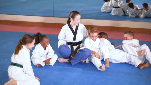 teacher, children in taekwondo class, sit on floor - girl sitting cross legged stock videos & royalty-free footage