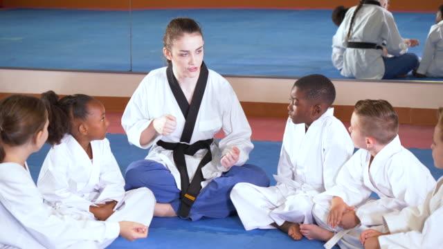 teacher, children in taekwondo class, sitting on floor - cross legged stock videos & royalty-free footage