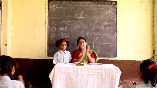 vidéos et rushes de teacher clapping with school students in classroom, haryana, india - écolière