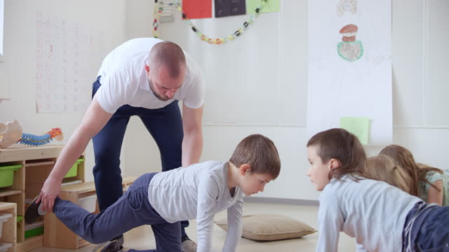 teacher correcting a pupils when he extends his legs while on all fours in the classroom - teaching stock videos & royalty-free footage