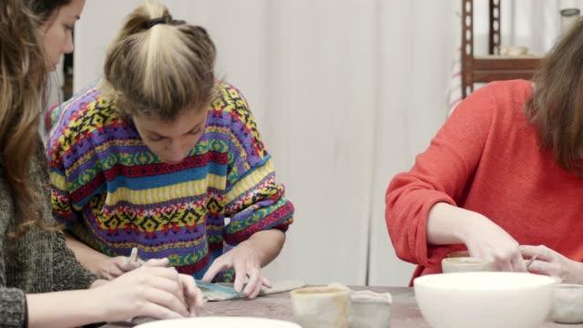 vídeos de stock e filmes b-roll de teacher cutting clay by students in studio - professora