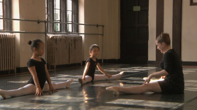 ws zo slo mo teacher does stretching exercises with her students (6-7)  in ballet studio / chicago, illinois, usa - ballet studio stock videos and b-roll footage