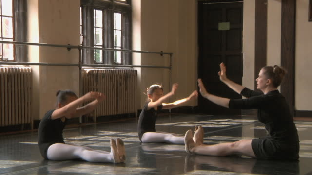 ws pan td slo mo teacher does stretching exercises with her students (6-7) in ballet studio / chicago, illinois, usa - ballet studio stock videos and b-roll footage