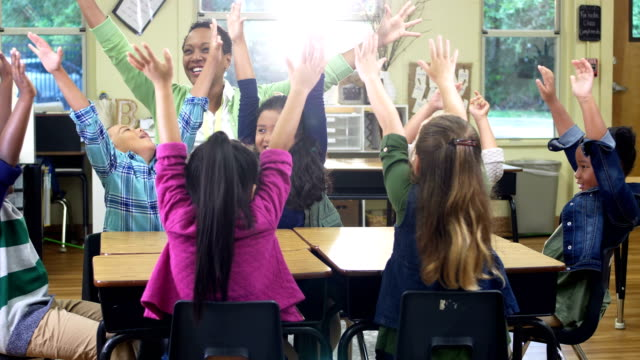 vídeos de stock e filmes b-roll de teacher, elementary students in classroom, hands raised - 6 7 years