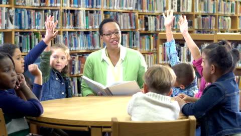 vídeos y material grabado en eventos de stock de profesor, estudiantes de primaria en la biblioteca levantando la mano - voluntario