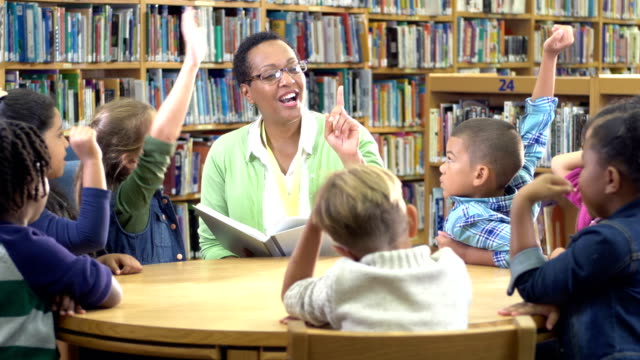 vídeos de stock e filmes b-roll de teacher, elementary students in library raising hands - 6 7 years