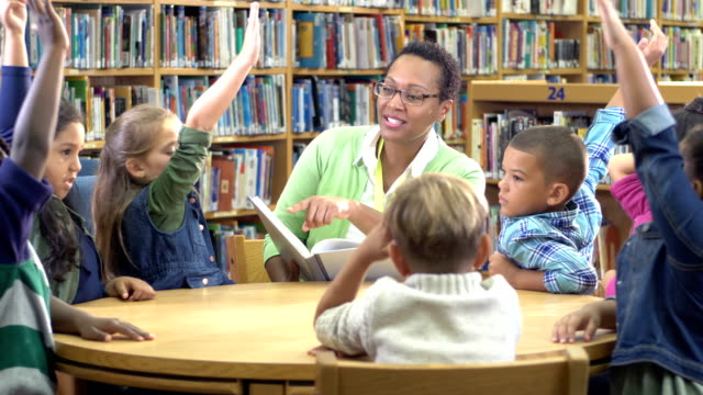 teacher, elementary students in library raising hands - 6 7 years stock videos & royalty-free footage