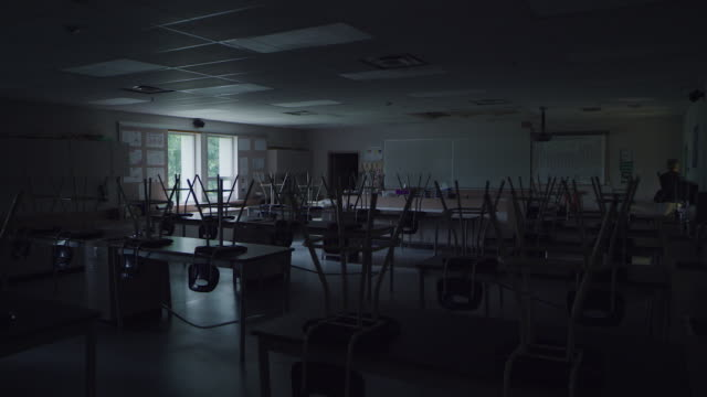 teacher enters empty school classroom - classroom stock videos & royalty-free footage