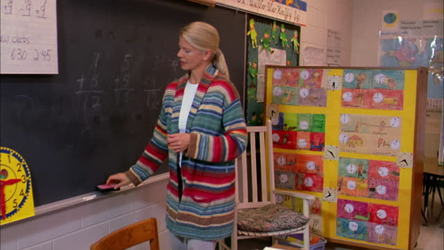 A teacher erases a blackboard then sits at her desk marking papers.