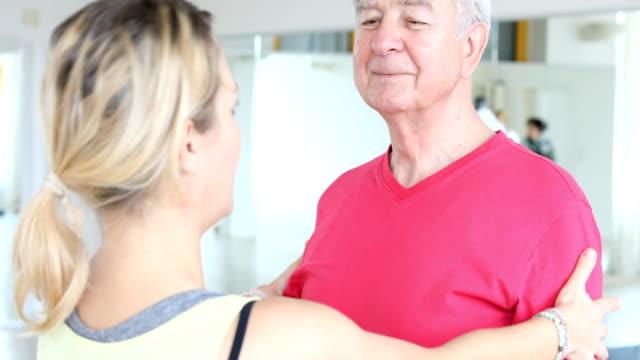 Teacher explaining shoulder exercise to senior man