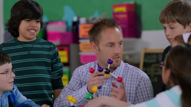 a teacher explains a molecular model to a group of elementary students. - goatee stock videos & royalty-free footage