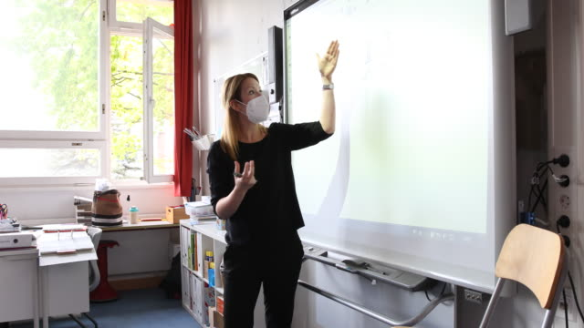teacher explains mathematics during a lesson with pupils , who are sitting at desks socially-distanced, on the second day of classes since march at... - teacher stock videos & royalty-free footage