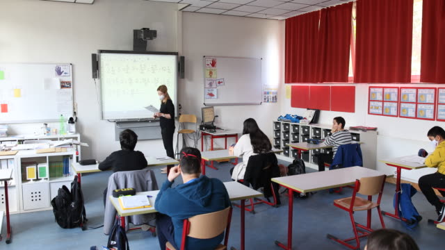 vidéos et rushes de teacher explains mathematics during a lesson with pupils , who are sitting at desks socially-distanced, on the second day of classes since march at... - établissement scolaire