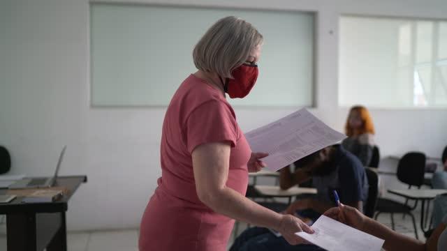 vídeos y material grabado en eventos de stock de profesor dando una prueba a los estudiantes - usando máscara facial - dar