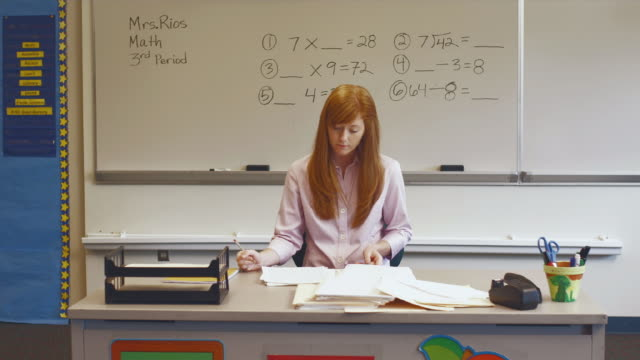 ws zi teacher grading papers at desk, smiling / edmonds, washington, usa  - see other clips from this shoot 1750 stock videos and b-roll footage