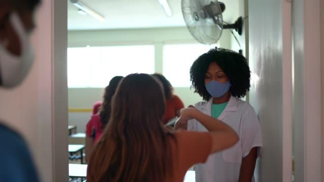 vídeos de stock e filmes b-roll de teacher greeting students with fist bump - professora